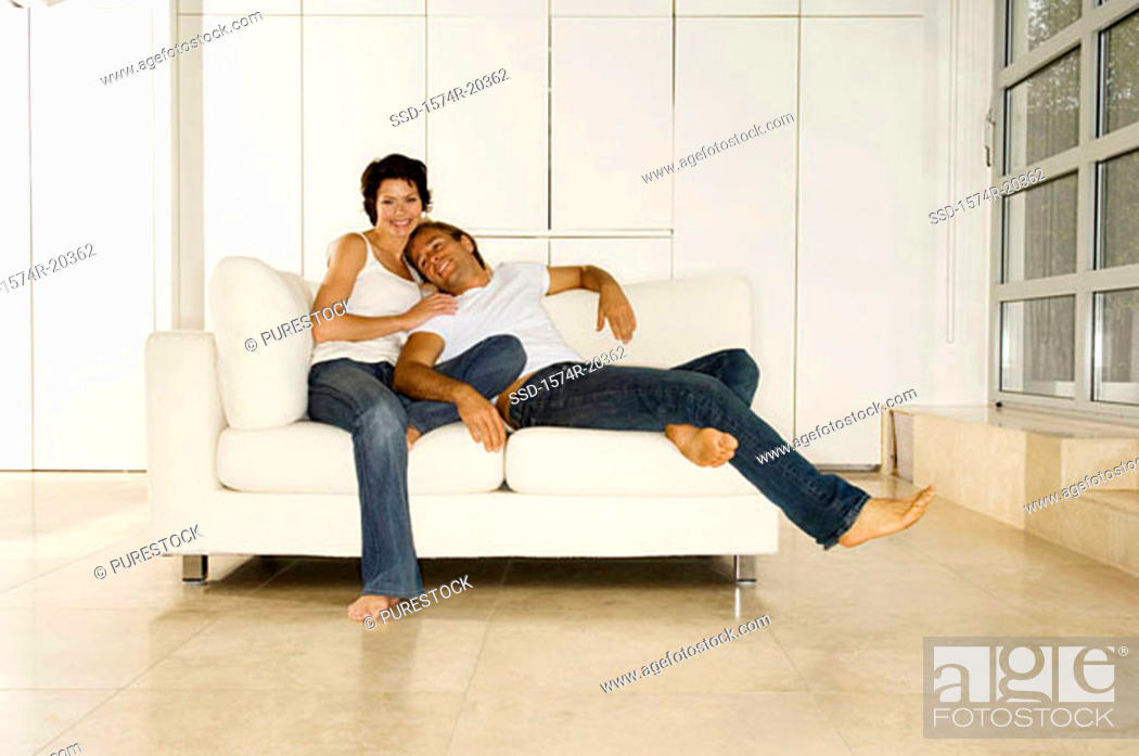 Stock Photo: Young man leaning against a young woman sitting on a couch.