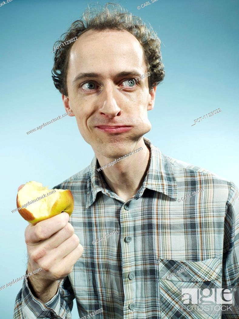 Stock Photo: A man with a cheek bulging with a bite of apple, looking to the side.