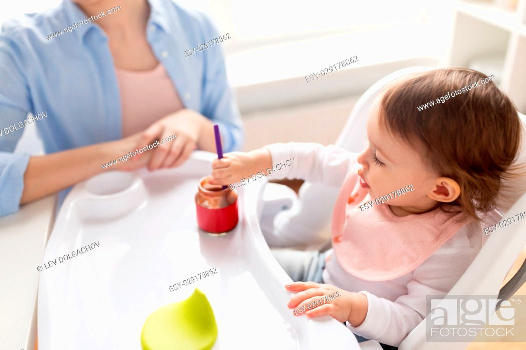 Stock Photo: food, child, feeding and people concept - little baby girl with spoon sitting in highchair and eating puree from jar and mother at home kitchen.