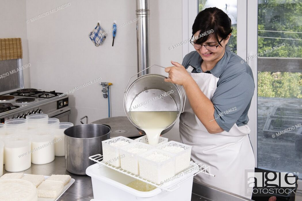 Stock Photo: Cheesemaker pours the curdled milk into plastic forms to shape the cheese.
