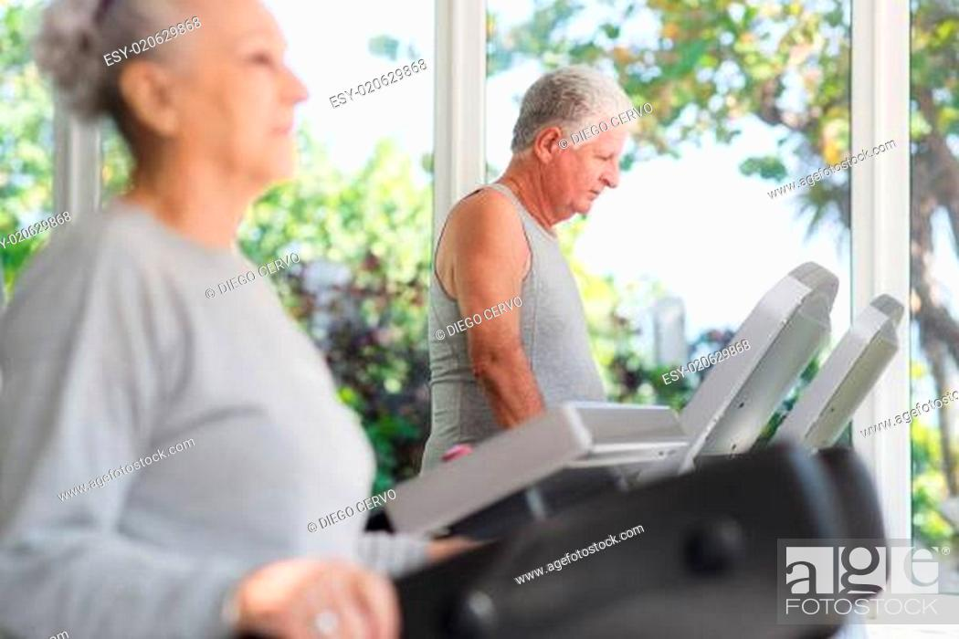 Stock Photo: senior man exercising in wellness club.