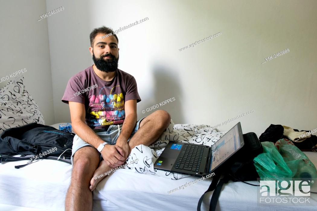 Stock Photo: Tilburg, Netherlands. Brazilian male traveller sitting on the bed of his Airbnb guest room with his laptop computer at arms length.