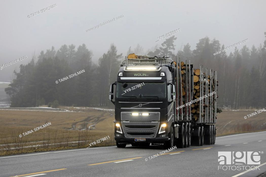 Stock Photo: Salo, Finland - March 15, 2019: Beautiful headlights and led lights of Volvo FH16 750 logging truck of Wolin Ky light up rural road on a foggy day.