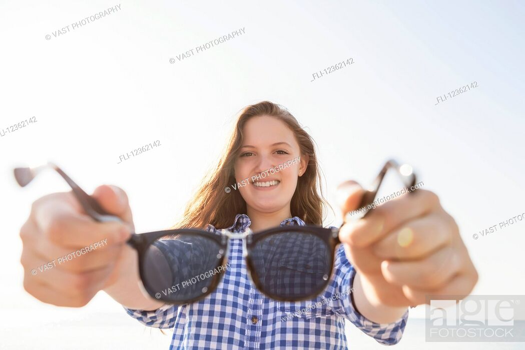 Stock Photo: Girl offering her sunglasses by holding them out away from her towards the camera, Woodbine Beach; Toronto, Ontario, Canada.