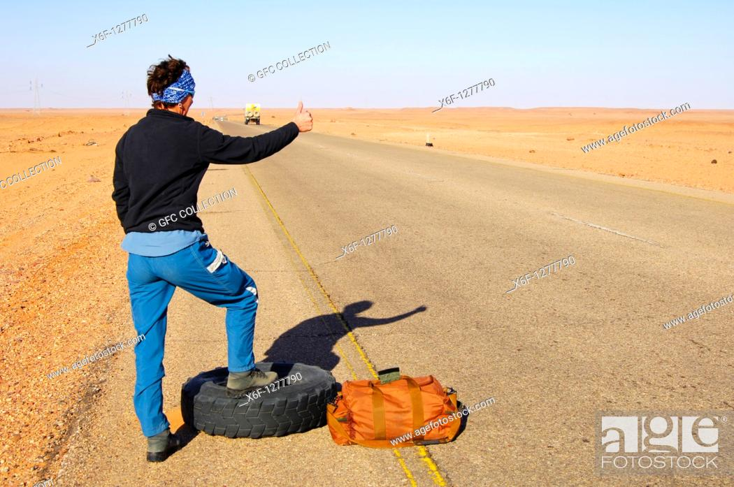 Stock Photo: Woman standing with a travelling bag next to a flat tyre at the edge of a lonly country road trying to stop a car for help, Al Awaynat Libya.
