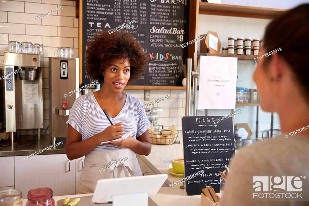 Stock Photo: Waitress writing customer's order at counter of coffee shop.