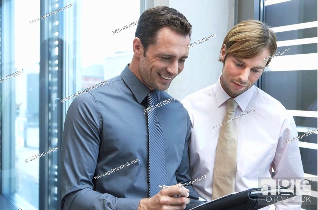Stock Photo: Germany, Cologne, Two businessmen holding documents, looking down, smiling, portrait.