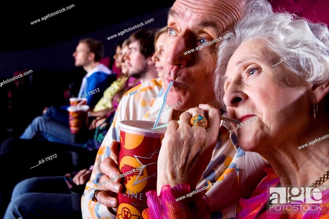 Stock Photo: Senior couple sharing drink in cinema, close-up.