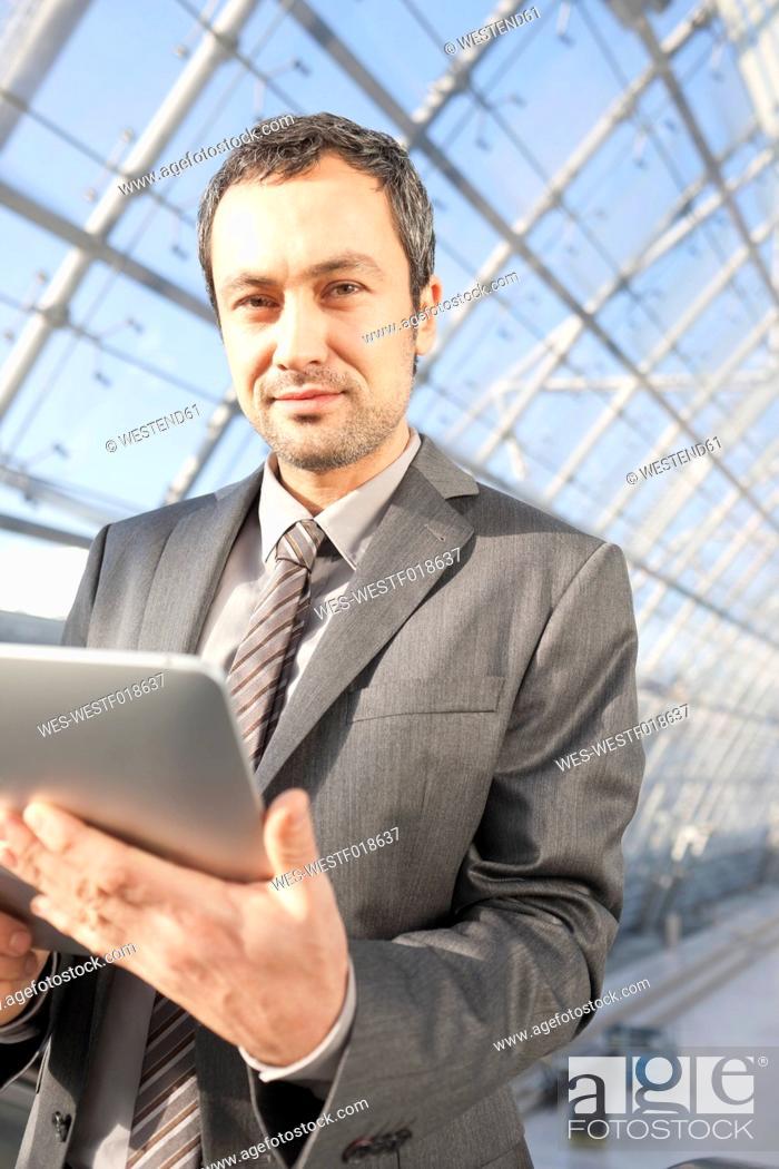 Stock Photo: Germany, Leipzig, Businessman using digital tablet on escalator, portrait.