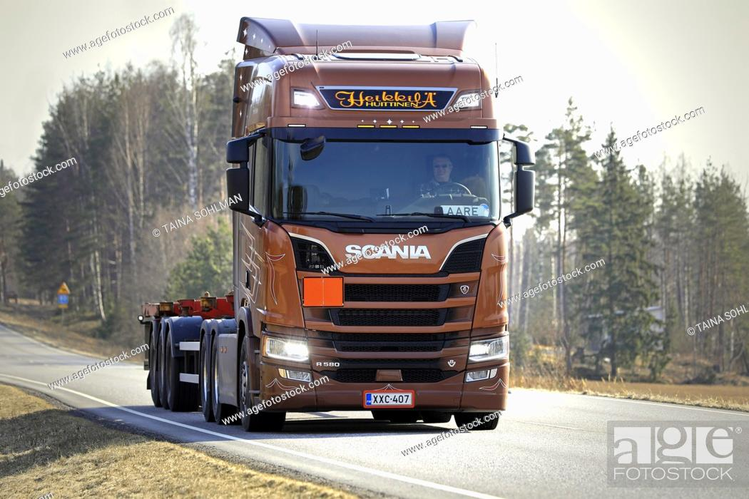 Stock Photo: Salo, Finland - April 5, 2019: Bronze Next Generation Scania R580 truck of AH Trans Oy for chemical container transport on road, high beams briefly on.