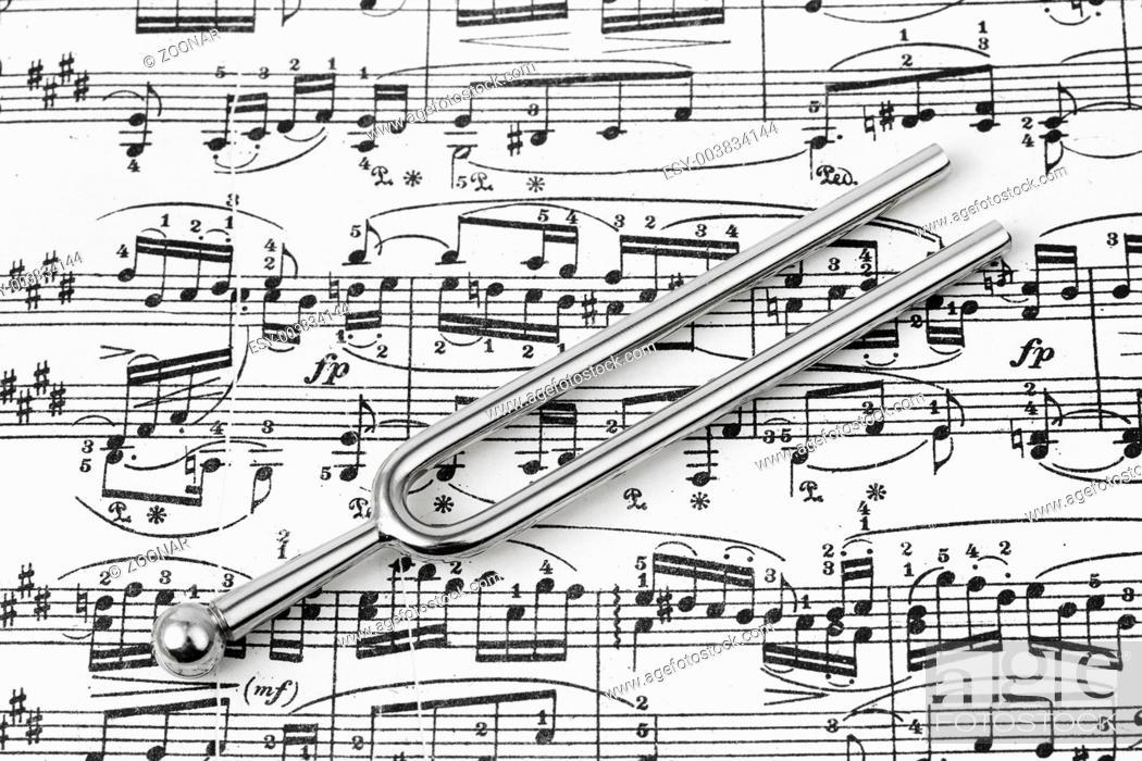 Stock Photo: Pitchfork on sheet music.
