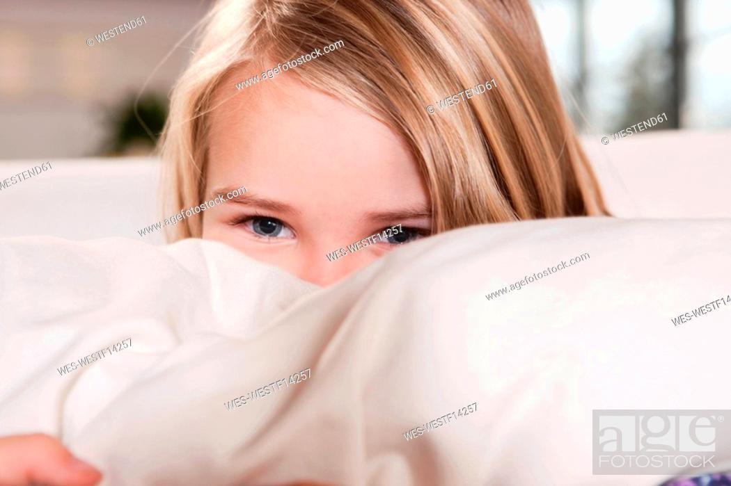 Stock Photo: Germany, Cologne, Girl 4-5 peeking from behind cushion, portrait, close-up.