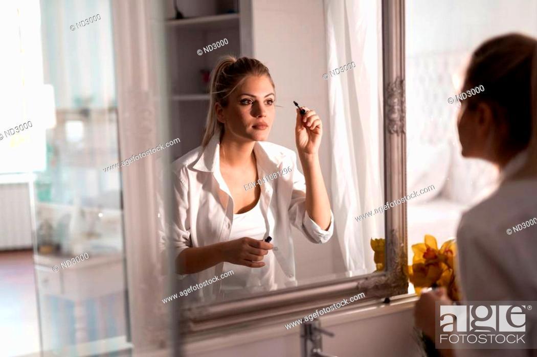 Stock Photo: Beautiful woman applying makeup at home.