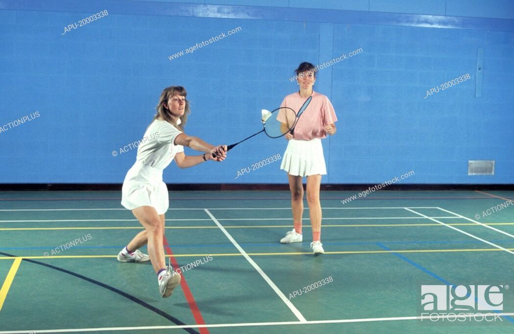 Stock Photo: Two women playing badminton.
