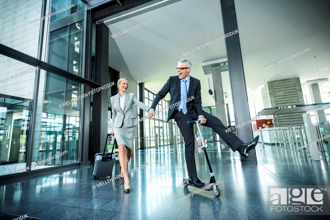Stock Photo: Germany, Stuttgart, Businesswoman with wheeled luggage, man riding scooter at office building.