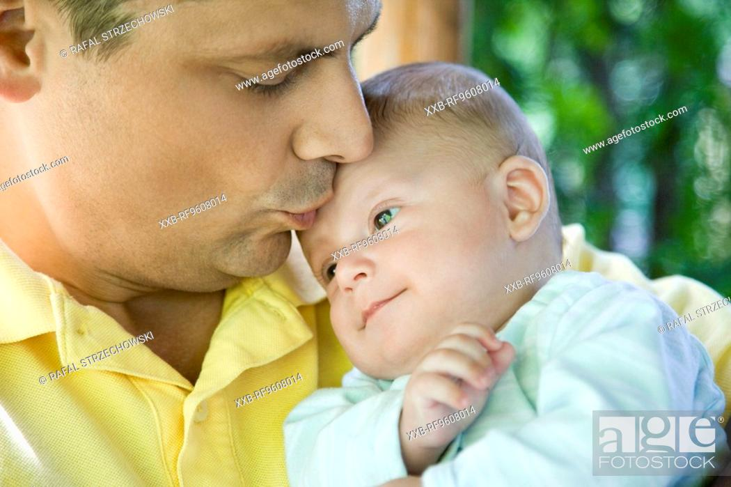 Stock Photo: Father kissing son.