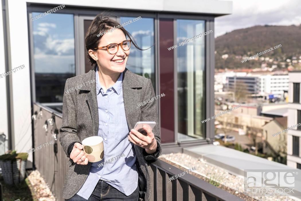 Stock Photo: Smiling businesswoman with cell phone and cup of coffee on roof terrace.