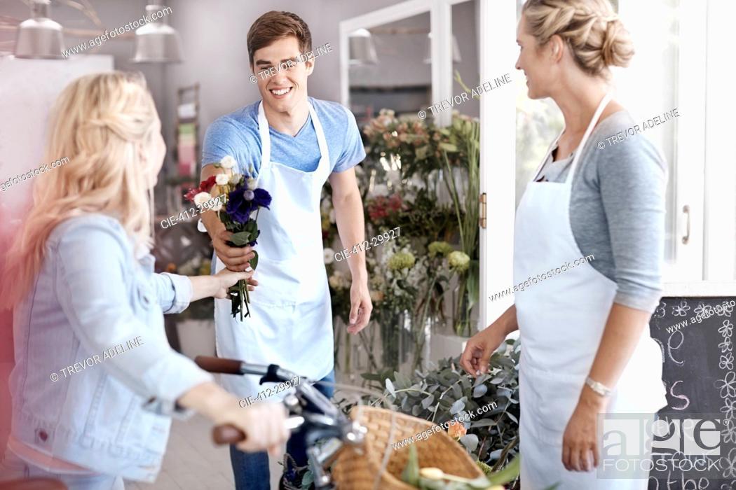 Stock Photo: Florist giving customer bouquet in flower shop.
