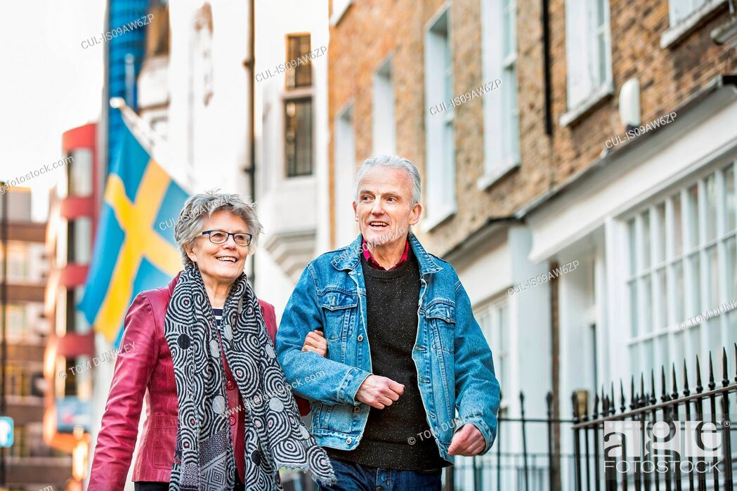 Stock Photo: Senior couple strolling arm in arm along city street.