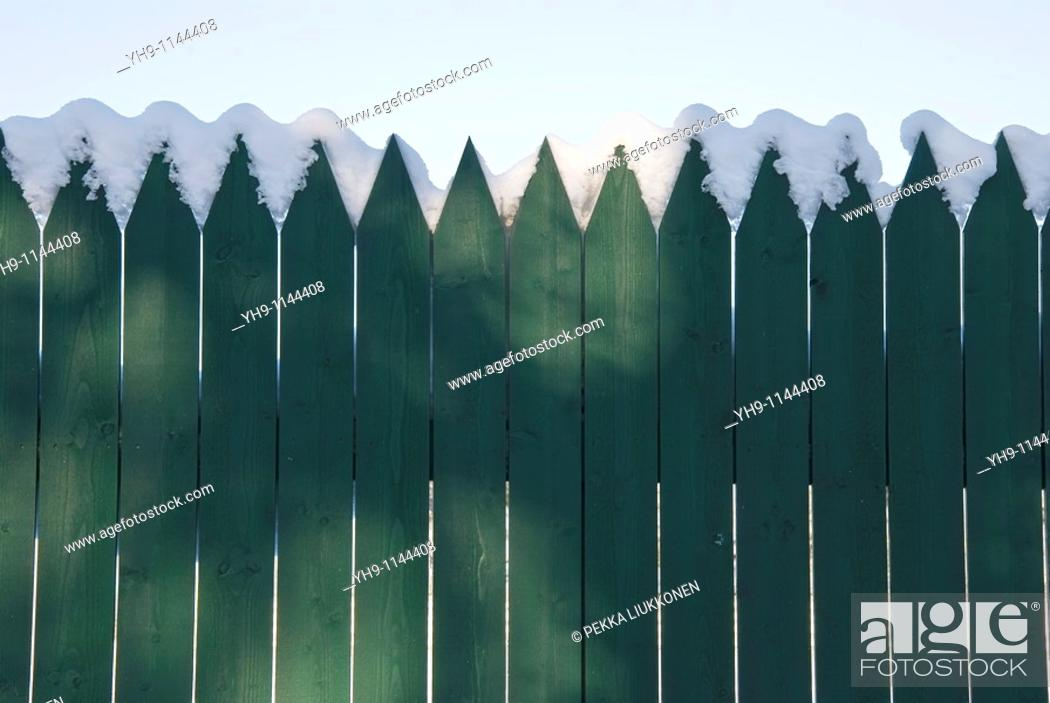 Stock Photo: Some snow on a green fence.