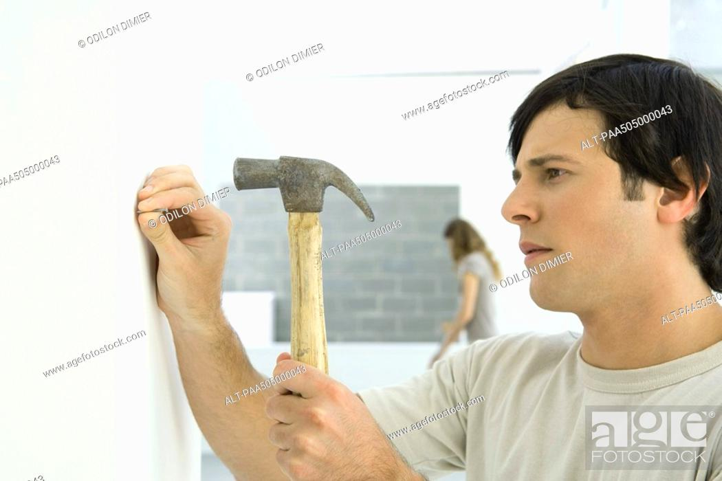 Stock Photo: Man hammering nail into wall, woman in background.