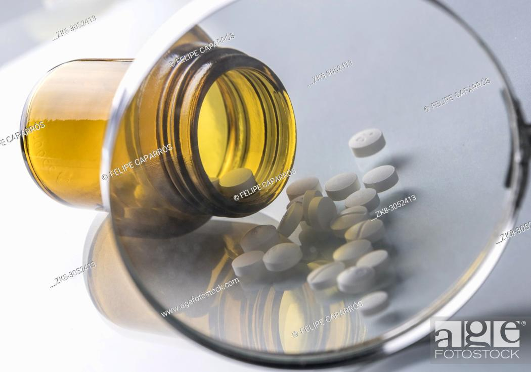 Stock Photo: Pill bottle seen through a magnifying glass isolated in white background, conceptual image.