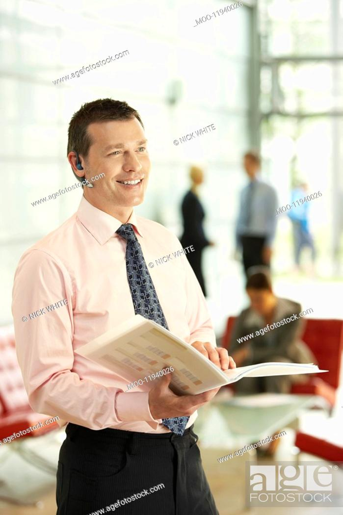 Stock Photo: Businessman Holding Report and Using Wireless Headset.