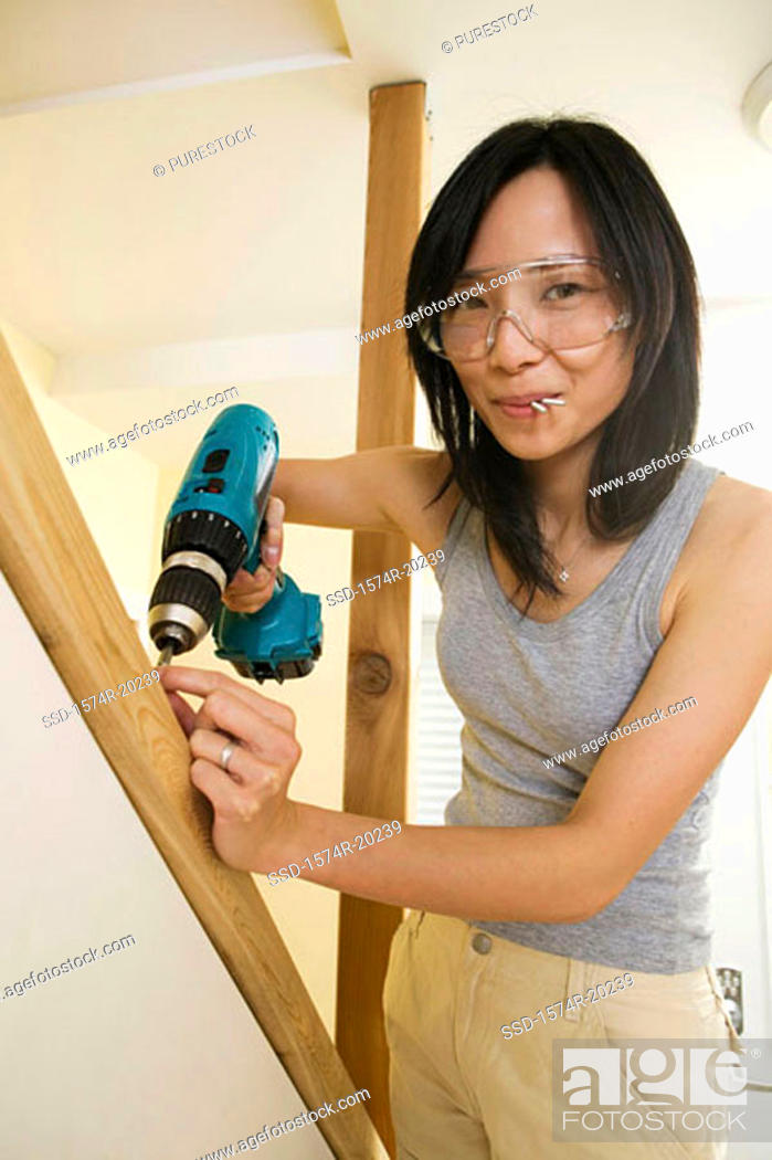 Stock Photo: Portrait of a young woman drilling into a plank.
