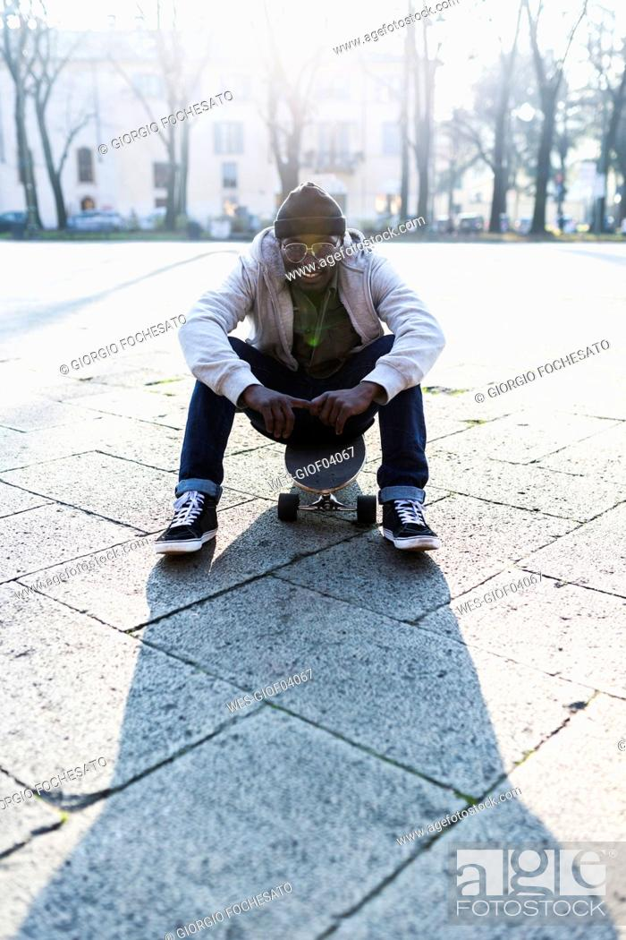 Stock Photo: Young amn with skateboard on urban square.