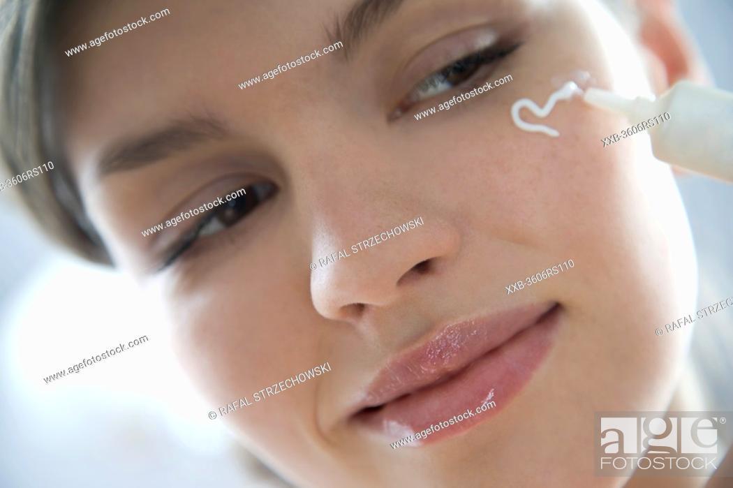 Stock Photo: woman applying cream under eyes.