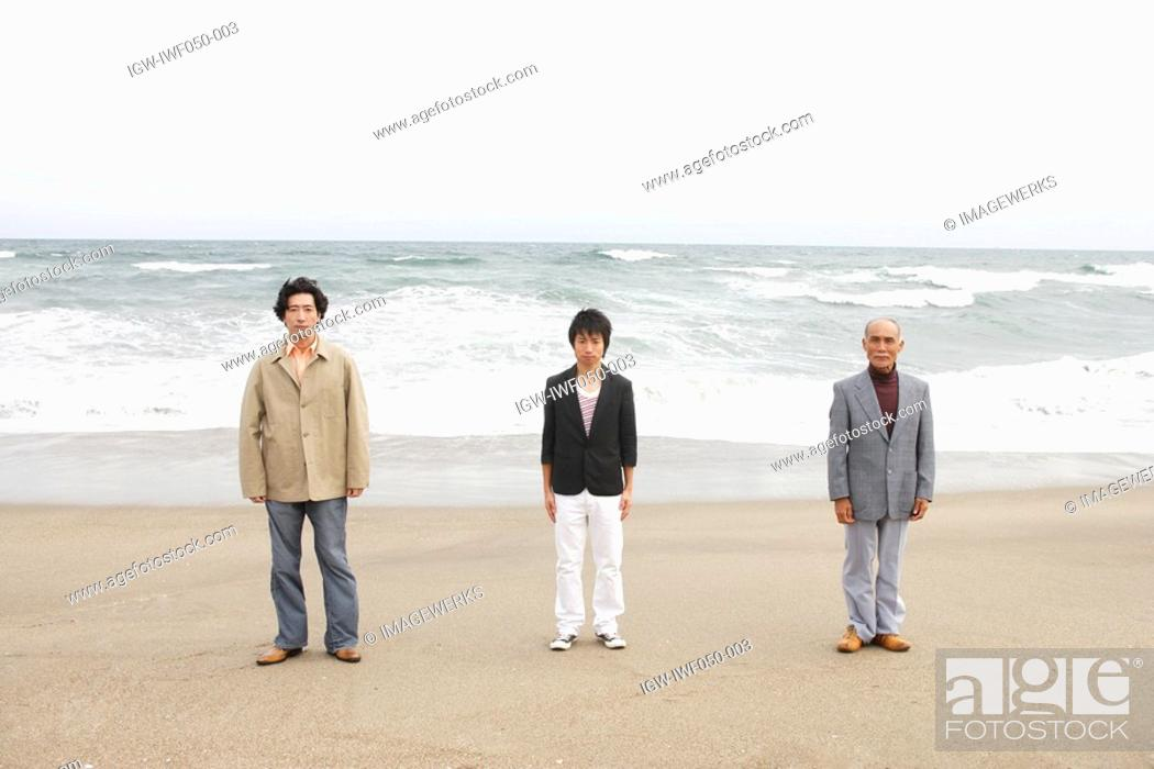 Stock Photo: Young man standing with father and grandfather at beach.