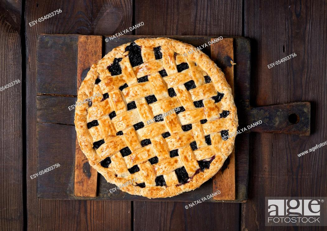 Stock Photo: whole baked round black currant cake on brown wooden background, top view.