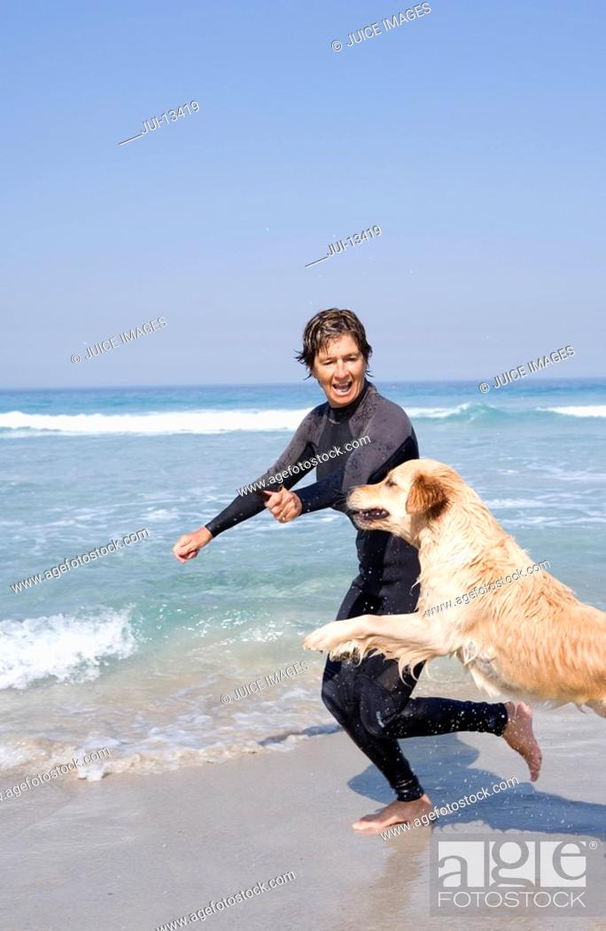 Stock Photo: Woman in wetsuit playing with dog on beach.