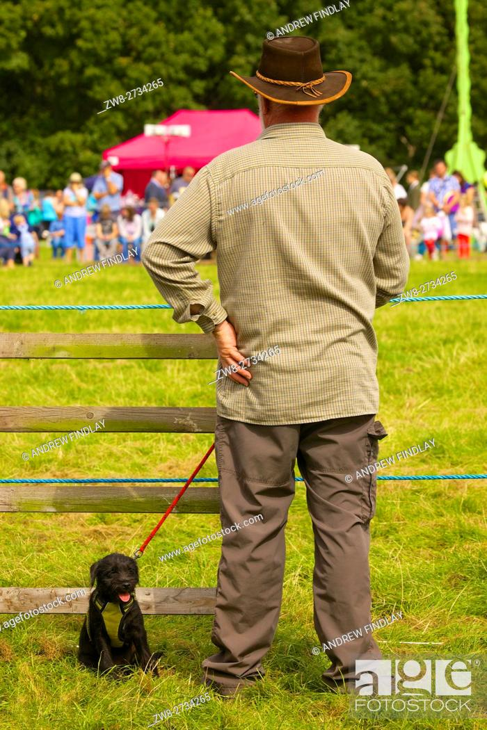 Stock Photo: Man wearing a hat with Patterdale Terrier puppy. Watching country show. Bellingham Show and Country Festival, Bellingham, Northumberland, England.