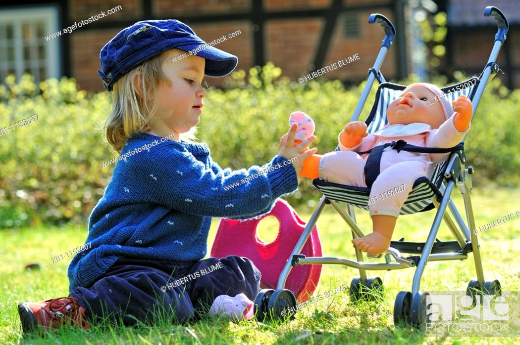 Photo de stock: little girl, 2 years old, takes care of her doll in the doll buggy.