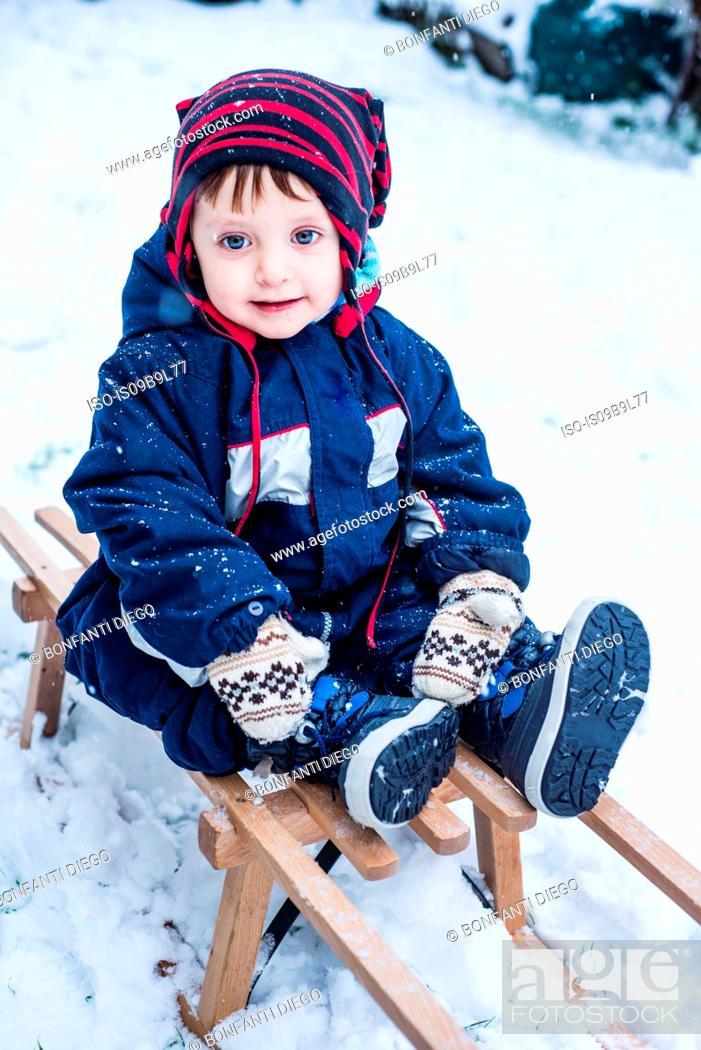 Imagen: Portrait of boy wearing ski suit on toboggan.