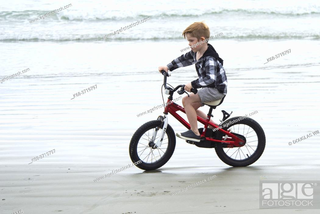 Imagen: A 6 year old boy rides his bike on the beach at Tofino, BC, Canada. .