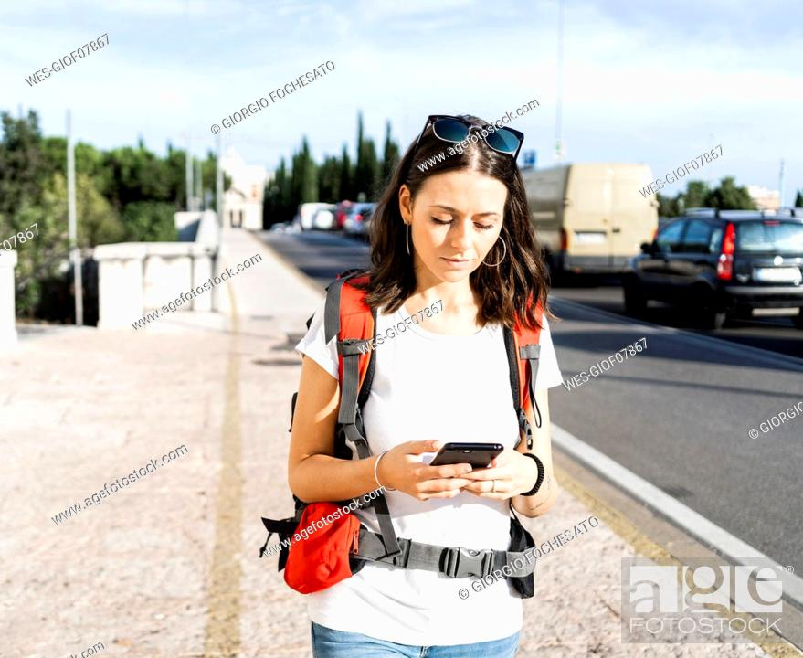 Stock Photo: Young female backpacker with red backpack using smartphone in the city, Verona, Italy.