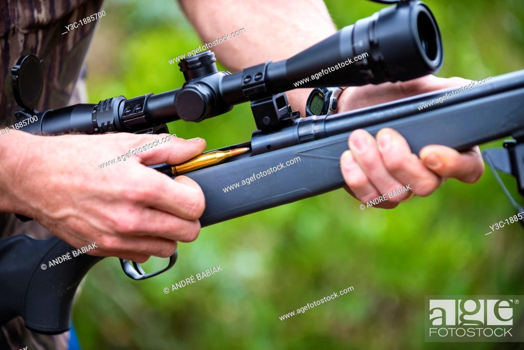 Stock Photo: Close up of loading a hunting rifle firearm gun with ammunition bullets.