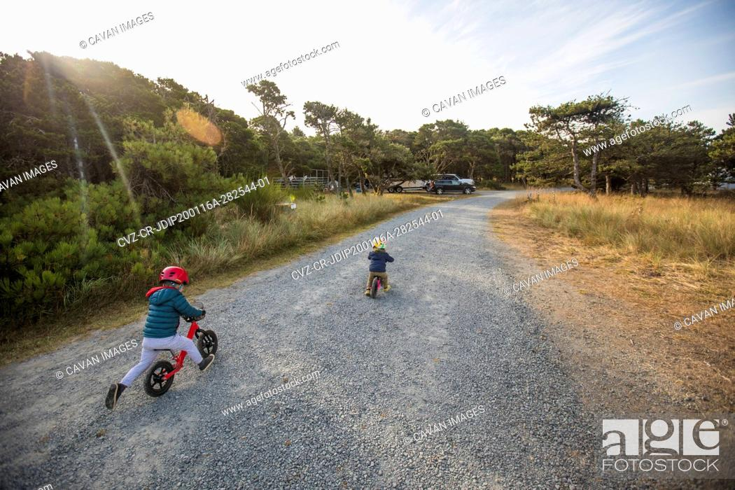 Imagen: Rear view of brother and sister biking on gravel road at dawn.