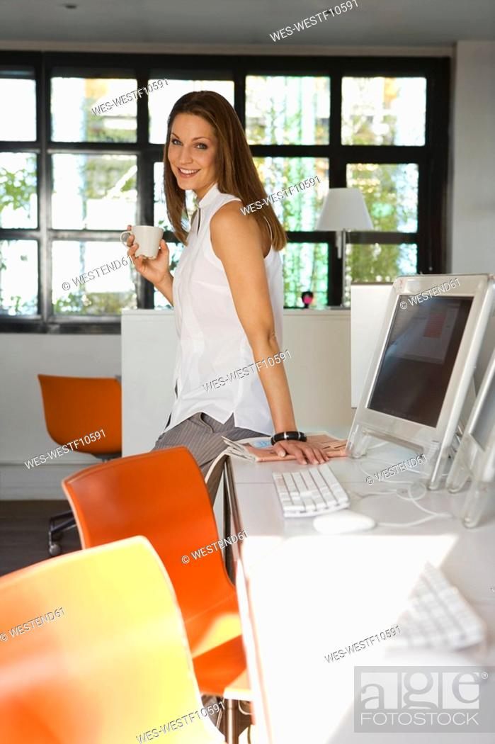 Stock Photo: Young woman in office holding plastic cup, smiling.