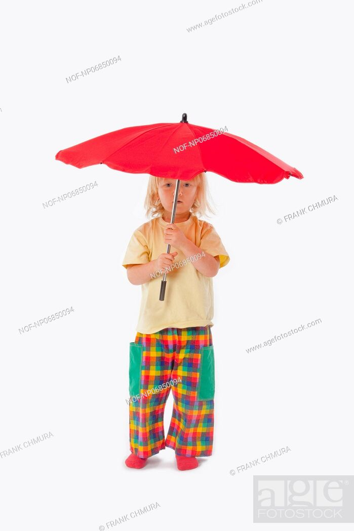 Stock Photo: boy with long blond hair playing with a red umbrella.