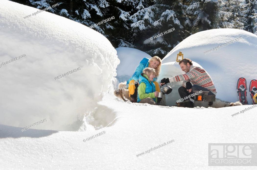 Stock Photo: Austria, Salzburg County, Family sitting near igloo.