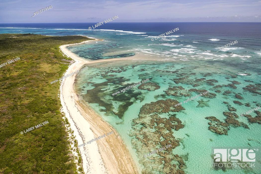 Stock Photo: Aerial view of a deserted beach, coral formations and turquoise waters along the coastline on the Atlantic Ocean side of Cat Island, Bahamas.