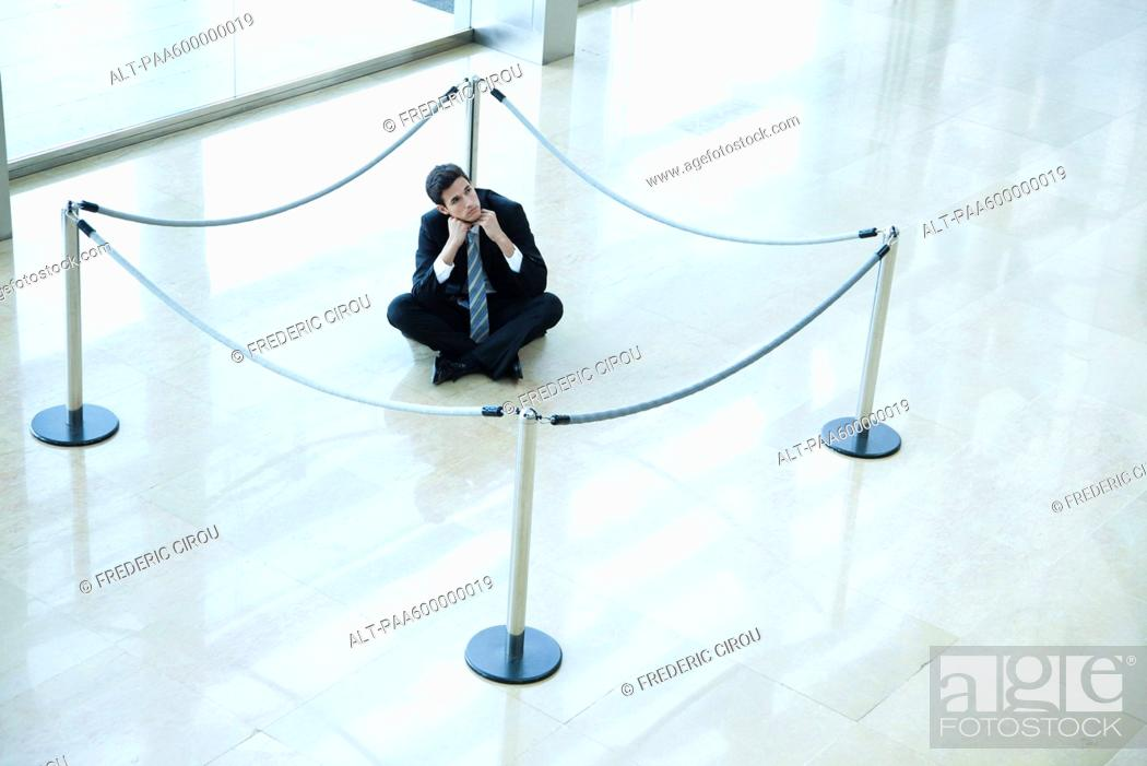 Stock Photo: Businessman sitting on floor inside roped off area in lobby.