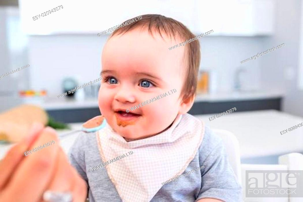 Stock Photo: Happy baby being fed by mother.