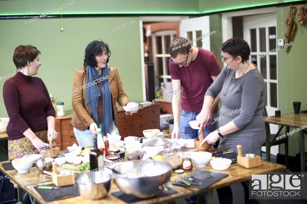 Stock Photo: woman teaching group a cooking workshop course on how to make homemade hummus onself.