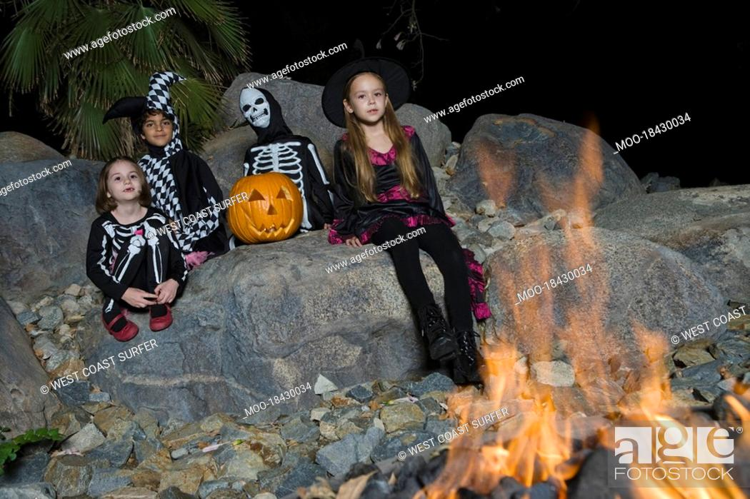 Photo de stock: Portrait of boys and girls 7-9 wearing Halloween costumes by campfire.