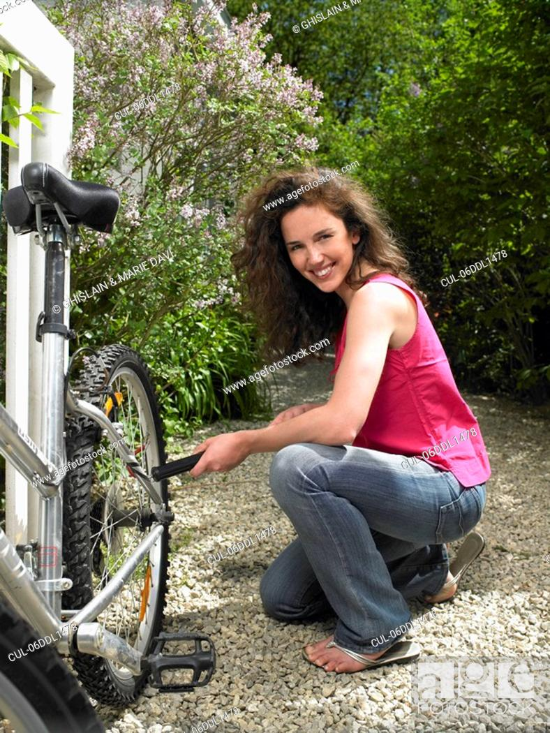 Stock Photo: Woman pumping up her bicycle wheel.