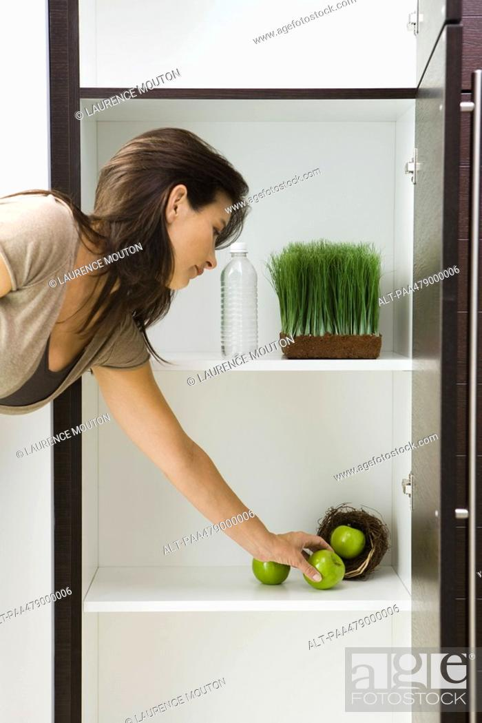 Stock Photo: Woman reaching for apple in pantry containing apples in nest, tray of wheat grass and bottle of water.